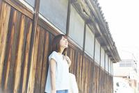 塀の前でたたずむ女性 10179008671| 写真素材・ストックフォト・画像・イラスト素材|アマナイメージズ