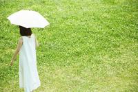 草原の中傘をさし歩く若い女性