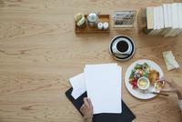 机の上のカフェご飯と書類 10179008813| 写真素材・ストックフォト・画像・イラスト素材|アマナイメージズ