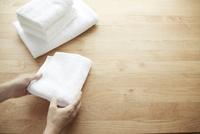 テーブルの上でタオルをたたむ女性