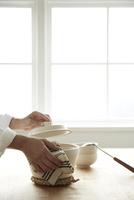 鍋をテーブルに置く女性