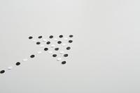 白と黒の丸い紙で作った矢印