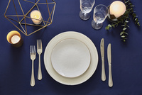 紺色のテーブルクロスの上でセッティングされた皿とカトラリー 10179009454| 写真素材・ストックフォト・画像・イラスト素材|アマナイメージズ