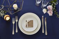 紺色のテーブルクロスの上でセッティングされた皿とカトラリー 10179009455  写真素材・ストックフォト・画像・イラスト素材 アマナイメージズ