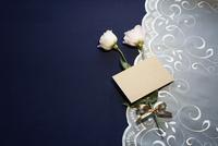 紺色テーブルクロスの上に置かれたレースとピンクの花とメッセージカード