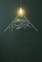 光るペンダントライトと黒板に描かれたメリークリスマスの文字