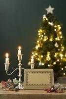 テーブルの上に置かれた燭台と三本の蝋燭とメッセージカードと奥にあるクリスマスツリー