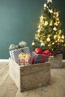 木の箱に入った三つのプレゼントボックスとクリスマスツリー