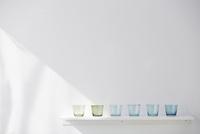 白い棚の上に並べられたブルーとグリーンのガラスのコップ 10179009763| 写真素材・ストックフォト・画像・イラスト素材|アマナイメージズ