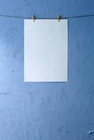 青い壁に吊られた紙 10179010081| 写真素材・ストックフォト・画像・イラスト素材|アマナイメージズ