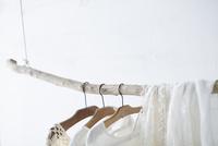 木の棒に吊り下がった白い服 10179010168| 写真素材・ストックフォト・画像・イラスト素材|アマナイメージズ