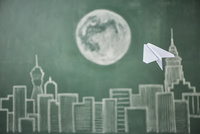 ビル群と満月が描かれた黒板イラストに飛ばした紙飛行機