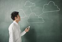 黒板に書かれた複数の繋がった雲の前でスマートフォンを触る人 10179010271| 写真素材・ストックフォト・画像・イラスト素材|アマナイメージズ