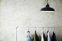 シルバーのラックにかかった服と照明 10179010673| 写真素材・ストックフォト・画像・イラスト素材|アマナイメージズ
