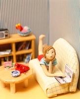 ソファに寝転び雑誌を見る女性のクラフト 10186000280| 写真素材・ストックフォト・画像・イラスト素材|アマナイメージズ