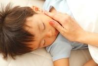 眠る男の子の頬に触れる母親の手
