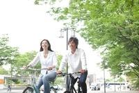 新緑の街を自転車で走る若いカップル