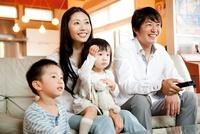 ソファでテレビを見る4人家族
