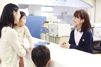病院の受付で来院者れに対応する女性職員