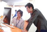 パソコンを見る私服のビジネスマン2人