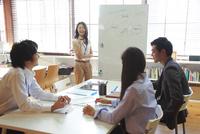 シェアオフィスでミーティングをする私服の男女ビジネスマン4人 10186004042| 写真素材・ストックフォト・画像・イラスト素材|アマナイメージズ