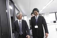 オフィス内を歩く4人のビジネスマン