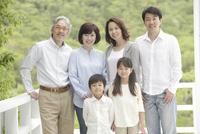 新緑のベランダで微笑む3世代家族