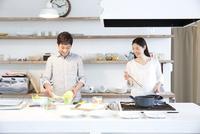 キッチンで調理する30代カップル