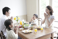 朝食で手を合わす4人家族