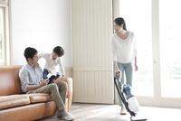 居間で掃除をする母親とくつろぐ4人家族