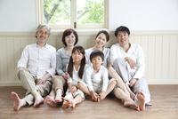 窓辺の床に座って微笑む3世代家族