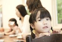 椅子の背から顔をのぞかせる幼い女の子