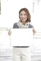 メッセージボードを持つ若い女性