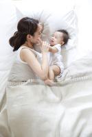 ベッドで赤ちゃんをあやす若い母親