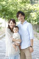 新緑の道で微笑む若い3人家族