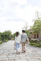 新緑の住宅街を歩く後姿の若いカップル