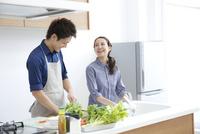 キッチンで微笑む若いカップル