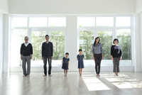 窓のある部屋に立つ3世代家族