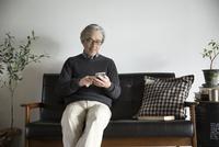 ソファでスマートフォンに触れるシニア男性 10186009128| 写真素材・ストックフォト・画像・イラスト素材|アマナイメージズ