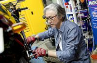 バイクを修理するシニア男性