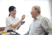 介護施設の朝食を食べるシニア男性とサポートする介護福祉士 10186009428  写真素材・ストックフォト・画像・イラスト素材 アマナイメージズ