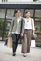 ショッピングバッグを持って歩くカップル 10186009670| 写真素材・ストックフォト・画像・イラスト素材|アマナイメージズ