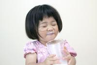ミルクを飲み干して満足する3才の女の子 10206001377| 写真素材・ストックフォト・画像・イラスト素材|アマナイメージズ