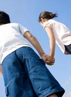 青空のもと手をつなぐ男の子と女の子