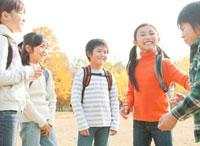紅葉の中で遠足を楽しむ小学生