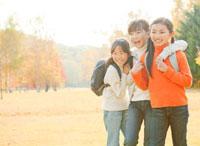 紅葉の中で遠足を楽しむ小学生の女の子3人