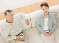 ソファーで談笑する60代の夫婦 俯瞰