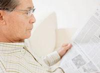 ソファーで新聞を読む60代の男性