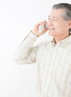 携帯電話で話す60代の男性