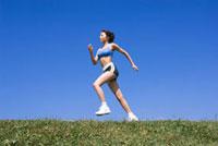 青空のもとでジョギングをする女性